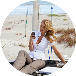 woman on beach with phone symbolizes the qualities of a great coach